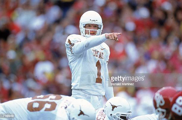 Quarterback Chris Simms the Texas Longhorns scrambles with the ball as he is sacked by Roy Williams of the Oklahoma Sooners at the Cotton Bowl in...