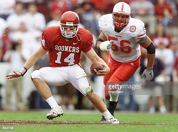 Quarterback Josh Heupel of the Oklahoma Sooners takes off running in front of defensive tackle Jeremy Slechta of the Nebraska Cornhuskers at Oklahoma...