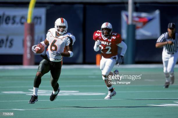 Santana Moss of the Miami Hurricanes carries the ball upfield during the game against the Temple Owls at the Veterans Stadium in Philadelphia,...
