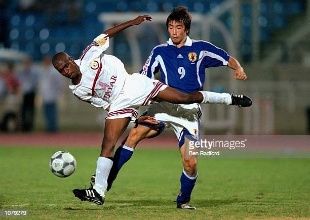 Saoud Fath of Qatar holds the ball from Akinori Nishizawa of Japan during the Asian Cup match played in Beirut Lebanon Mandatory Credit Ben Radford...
