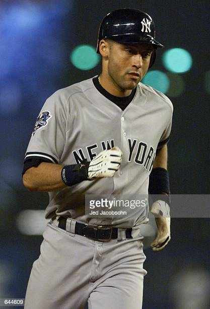 Shortstop Derek Jeter of the New York Yankees circle the bases after hitting a home run in the sixth inning against the New York Mets during Game 5...
