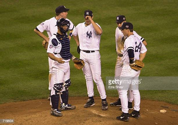 Starting pitcher Andy Pettitte of the New York Yankees confers with his teammates while throwing against the New York Mets during game one of the...