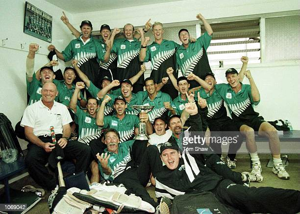 Stephen Fleming the captain of New Zealand holds the trophy as the rest of the team celebrate after beating India in the final of the ICC Knockout...