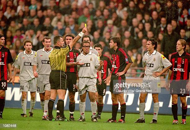 The AC Milan and Juventus players surround referee Stefano Braschi during the Italian Serie A game played at the San Siro Stadium in Milan Italy The...