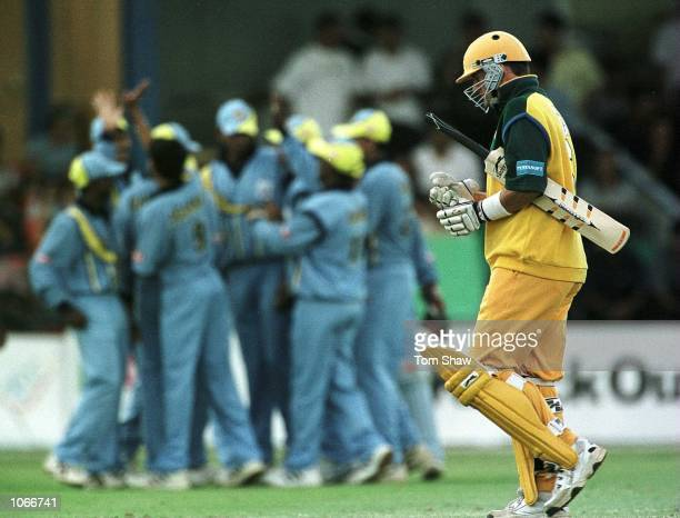 The India team celebrate as Mark Waugh of Australia makes his way back to the pavilion after being dismissed during the Australia v India second...