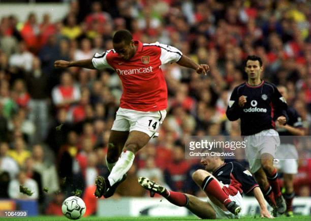Thierry Henry of Arsenal and Denis Irwin of Manchester United during the FA Carling Premiership game between Arsenal and Manchester United at...