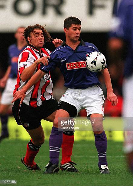 Tom Bennett of Walsall holds off Gavin Mahon of Brentford during the Nationwide Division Two match between Brentford and Walsall at Griffin Park...