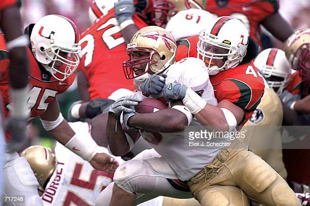 William McCray of the Florida State Seminoles gets pulled down with the ball by Howard Clark and Dan Inongaw of the Miami Hurricanes during the game...