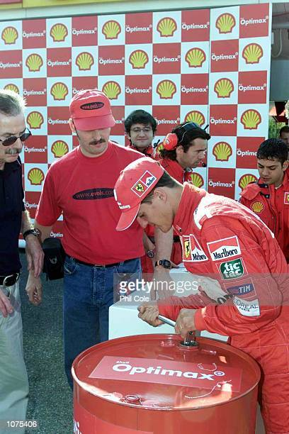 World Formula 1 Champion Michael Schumacher opens a barrel before putting it in his Ferrari at the Maranello circuit with the latest road fuel...
