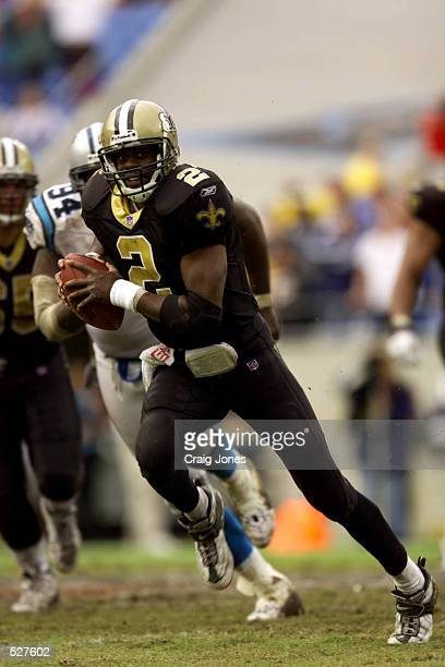 Aaron Brooks of the New Orleans Saints scrambles past Sean Gilbert of the Carolina Panthers during the game at Ericsson Stadium in Charlotte North...