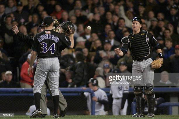 Catcher Damian Miller of the Arizona Diamondbacks returns the ball to pitcher Brian Anderson during game 3 of the World Series against the New York...