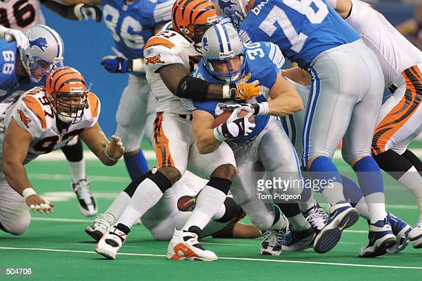 Cory Schlesinger of the Detroit Lions tries to break away from Takeo Spikes of the Cincinnati Bengals from during the game at the Pontiac Silverdome...