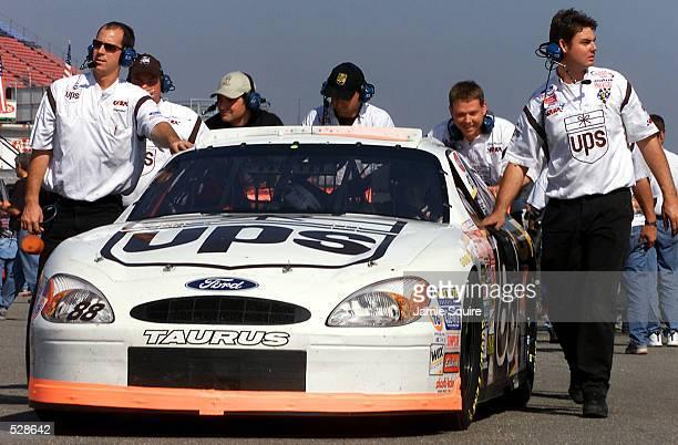 Dale Jarrett's crew pushes his Robert Yates Racing Ford Taurus following practice for Sunday's EA Sports 500 at Talladega Superspeedway in Talladega...