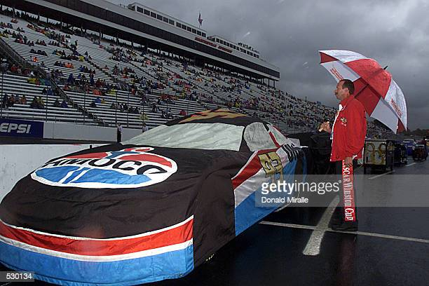 Dave Blaney's Bill Davis Racing Dodge Intrepid sits parked under a rain cover while a NASCAR official watches the skies during the rain delay of the...