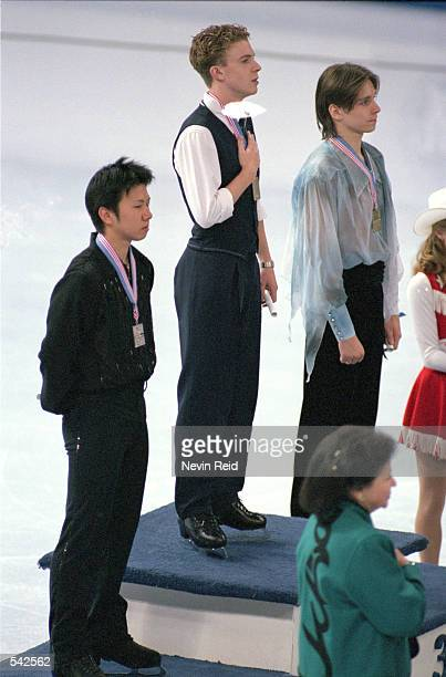 First place winner Timothy Goebel of the USA stands for the National Anthem with second place winner Takeshi Honda of Japan and third place winner...