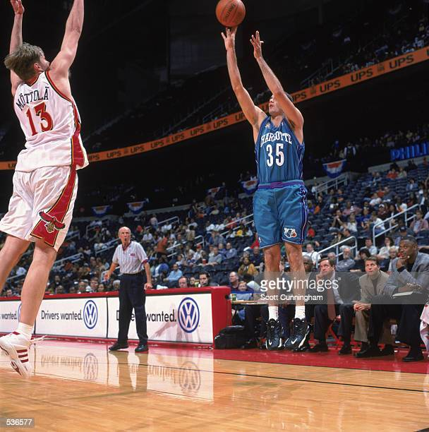 Forward Kirk Haston of the Charlotte Hornets shoots a jump shot over the outstretched arm of forward Hanno Mottola of the Atlanta Hawks during the...