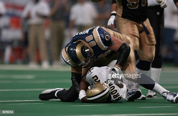 Grant Wistrom of the StLouis Rams hovers over quarterback Aaron Brooks of the New Orleans Saints during the game at the Dome at the America's Center...