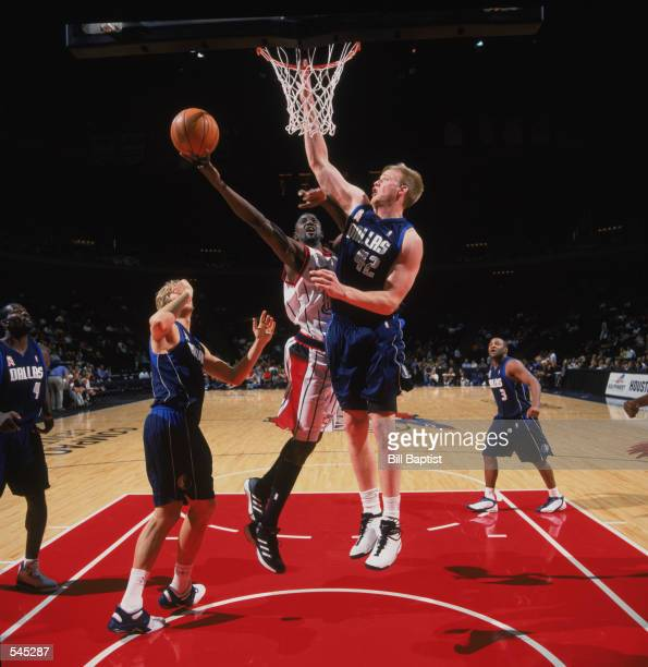 Guard Walt Williams of the Houston Rockets shoots around center Shawn Bradley of the Dallas Mavericks during the preseason game at the Compaq Center...