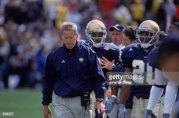 Head Coach Bob Davie of the Notre Dame Fighting Irish walks along with his team during the game against the Pittsburgh Panthers at the Notre Dame...