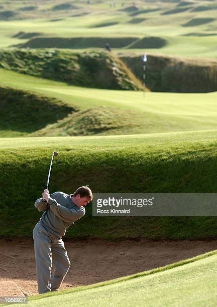 Kenny Dalglish plays out from a bunker on the sixth fairway at Kingsbarns Golf Links during the first official practise round during the inaugural...