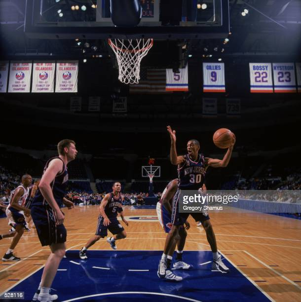 Kerry Kittles of the New Jersey Nets rebounds the ball with Jason Kidd and Todd MacCulloch during the PreSeason Game against the New York Knicks at...
