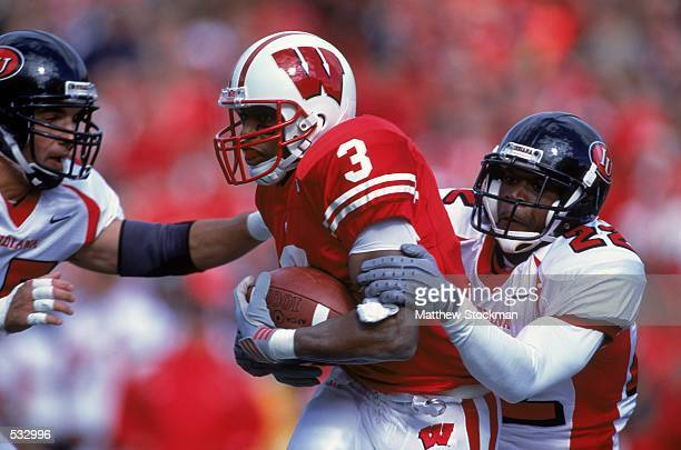 Lee Evans of Wisconsin Badgers gets tackled by Sharrod Wallace of the Indiana Hoosiers during the game at the Camp Randall Stadium in Madison...