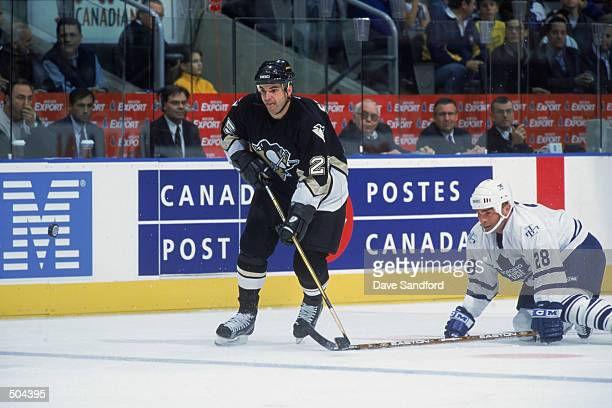Left wing Kevin Stevens of the Pittsburgh Penguins skates towards the play ahead of fallen right wing Tie Domi of the Toronto Maple Leafs during the...