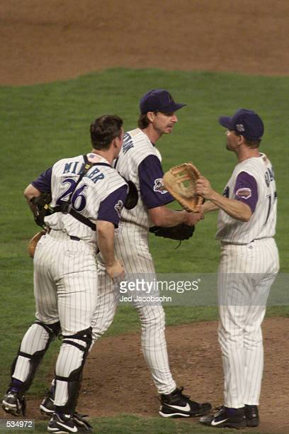 Randy Johnson of the Arizona Diamondbacks is congratulated by teammates Damian Miller and Mark Grace after beating the Yankees in game two of the...