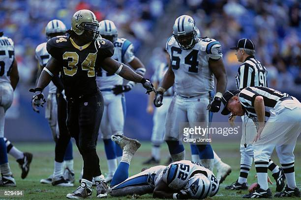 Ricky WIlliams of the New Orleans Saints looks on as Kory Minor of the Carolina Panthers rolls on the ground during the game at Ericsson Stadium in...