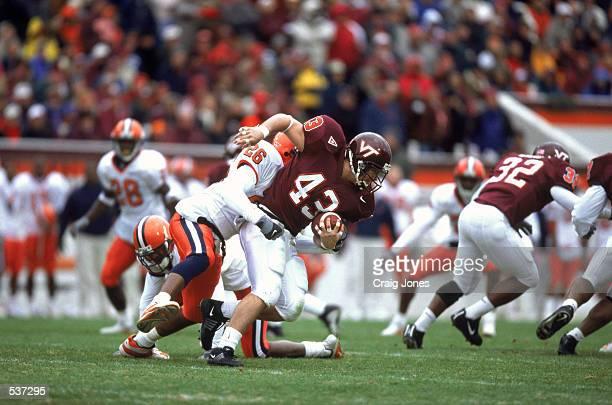 Running back Doug Easlick of the Virginia Tech Hokies tries to break free of the grasp of linebacker Maurice Minter of the Syracuse Orangemen during...