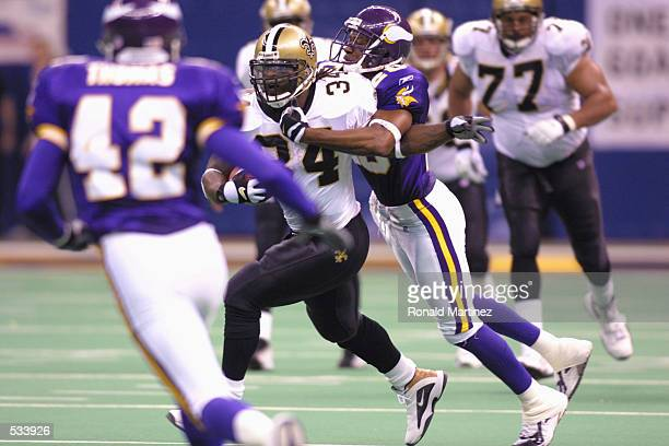 Running back Ricky Williams of the New Orleans Saints runs the ball as Kenny Wright of the Minnesota Vikings struggles to make a tackle at the...