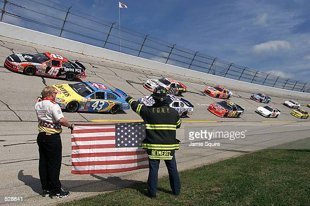 Safety crew members wish Nascar drivers luck as they pass on a parade lap prior to the start of the EA Sports 500 at Talladega Superspeedway in...
