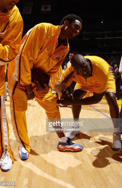 Shaquille O''Neal of the Los Angeles Lakers admires teammate Kobe Bryant's patriotic shoes before their game against the Portland Trail Blazers at...