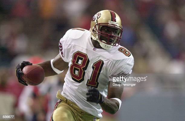 Terrell Owens of the San Francisco 49ers carries against the defense of the Atlanta Falcons for the game winning touchdown during the game at the...
