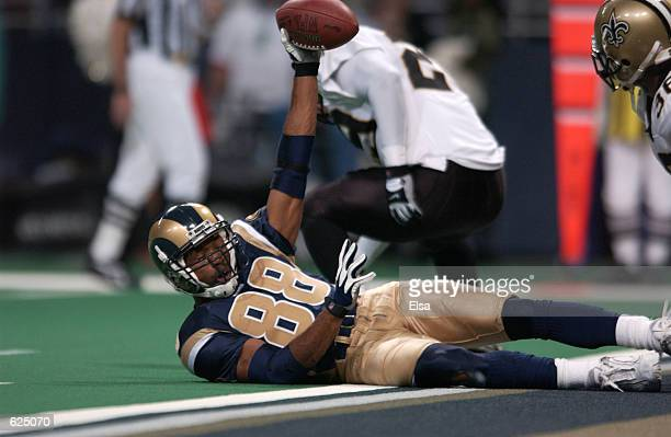 Torry Holt of the St Louis Rams holds aup the ball after a touchdown against the New Orleans Saints during the game at the Dome at the America's...