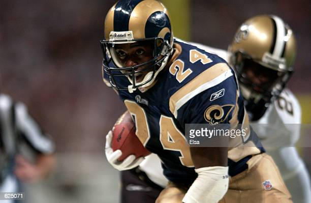 Trung Candidate of the StLouis Rams evades the New Orleans Saints during the game at the Dome at the America's Center in StLouis Missouri The Saints...