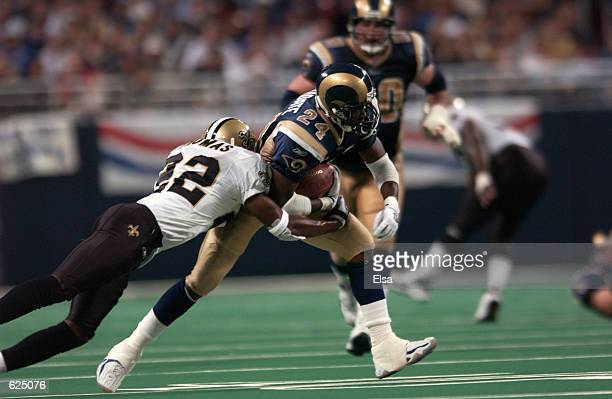 Trung Candidate of the StLouis Rams is being chased by Fred Thomas of the New Orleans Saints during the game at the Dome at the America's Center in...