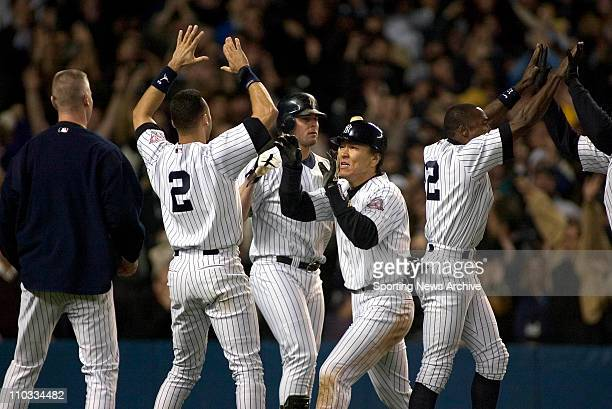 Hideki Matsui of the New York Yankees is greeted at home plate after scoring the tying run during the Yanks 6-5 victory over the Boston Red Sox in...