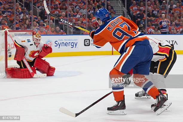 Oilers Capitan Connor McDavid of the Edmonton Oilers shoots the puck through a Calgary Flames defenceman during the Calgary Flames versus the...