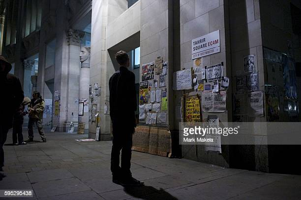 Oct 22 2011 London England UK A man reads placards on a wall named Tahrir Square after Egypt in the protestors camp of hundreds outside St Paul's...