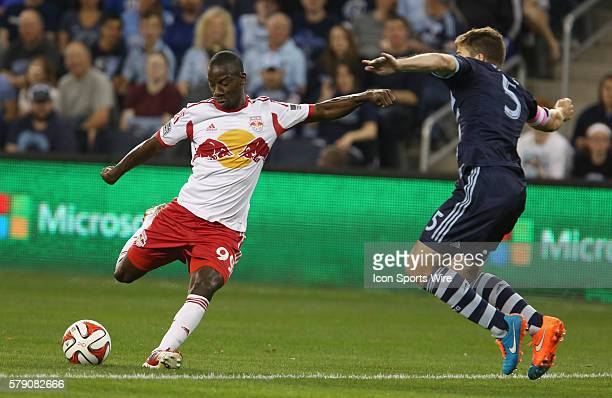 New York Red Bulls forward Bradley Wright-Phillips takes a shot on goal in front of Sporting KC defender Matt Besler during the match between the New...