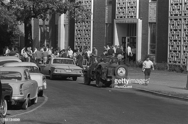 Oct 4 1962 Integration at Ole Miss[issippi] Univ[ersity] Oxford Miss Photograph shows students and soldiers in military vehicle outside of buildings...
