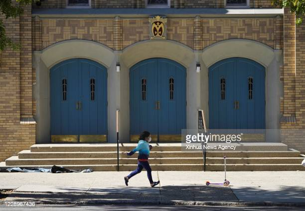 Oct. 8, 2020 -- A child runs past a church in a COVID-19 hotspot area of Queens in New York, the United States, on Oct. 8, 2020. The latest...