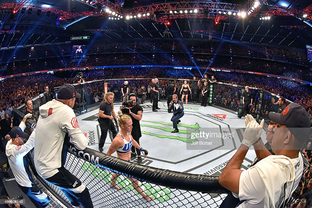 Octagon announcer Bruce Buffer (C) introduces Holly Holm (L) before facing Ronda Rousey (R) in their UFC women's bantamweight championship bout during the UFC 193 event at Etihad Stadium on November 15, 2015 in Melbourne, Australia.