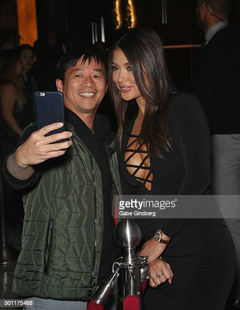Octagon Girl and model Arianny Celeste takes a selfie with a fan as she attends a UFC 194 after party at Hyde Bellagio at the Bellagio on December 12...