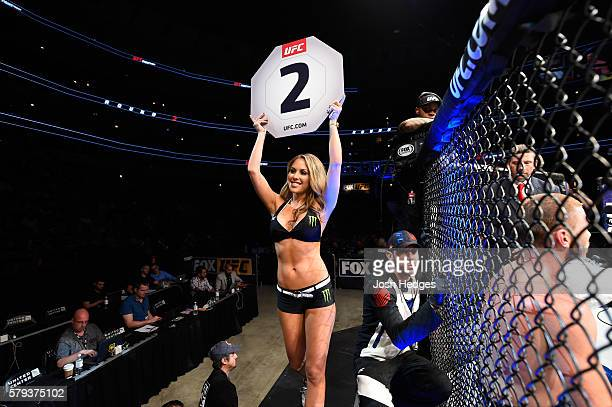Octagon Girl Brittney Palmer signals the start of round two between Michel Prazeres of Brazil and JC Cottrell in their lightweight bout during the...