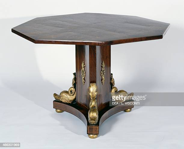Octagonal Restoration style Turin table with walnut and boxwood veneer finish inlaid top and carved and gilt wood dolphins Italy 19th century