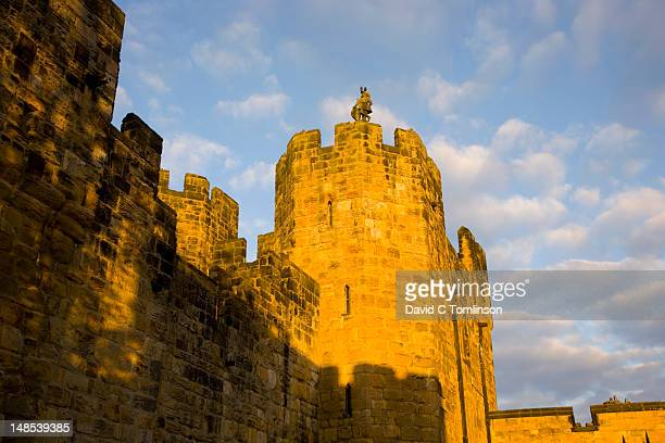Octagonal tower above gatehouse of Alnwick Castle at sunset.