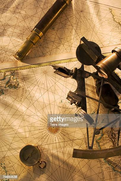 Octant, compass and telescope on nautical map