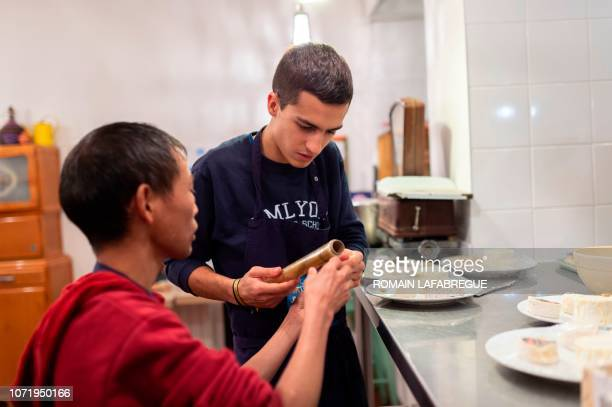 Octave a volunteer prepares a dinner with Nyima asylumseeker at an 'Escale Solidaire' in the 6th district of Lyon centraleastern France on November...